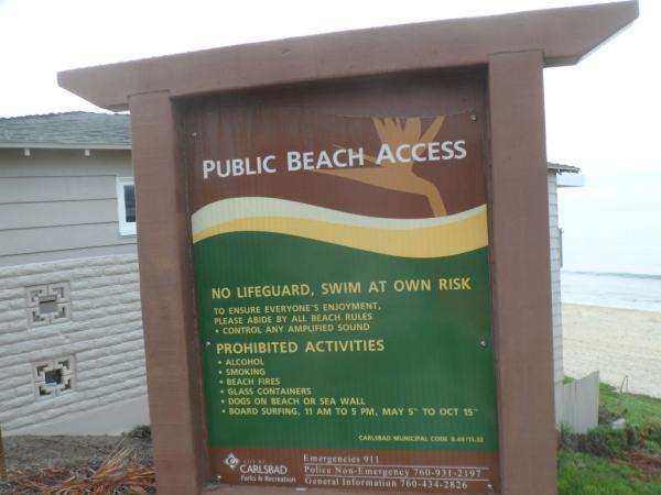 A Public Beach Access information sign provides details about nearby beaches.