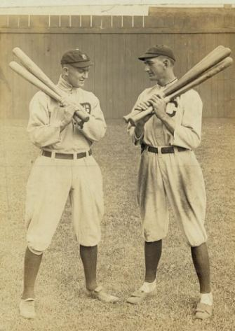 Shoeless Joe Jackson and Ty Cobb face off against each other, each with a handful of bats over one shoulder.
