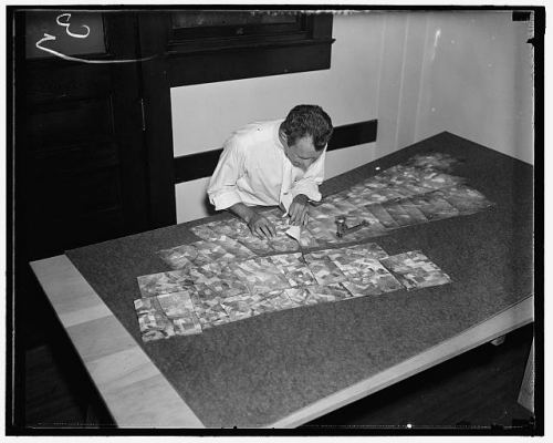 An AAA worker piecing together prints from the $3,000,000 map.