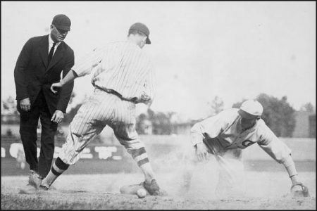 An umpire judging a play at second base, note the baseball on the ground behind the second baseman's right leg.