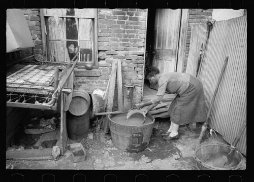 A woman collecting a bucket of water from a wash basin under a backyard water faucet, in a photo from Washington DC, originally published in 1935