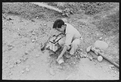 A young boy dipping water from an irrigation ditch, to be brought home for cooking and drinking, in a photo from Chamisal, New Mexico, originally published in July, 1940