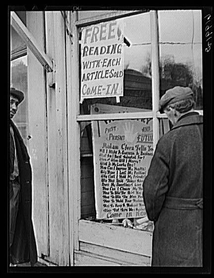 Two men outside a fortune teller's shop, with a sign advertising a free reading with every article sold.