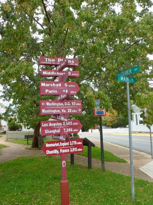 A street corner in The Plains, Virginia, with a sign showing distances to many other cities near and far.